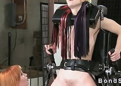 Blondie bound in standing frame flogged